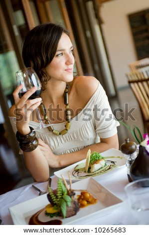 A young woman enjoying a meal and wine - stock photo