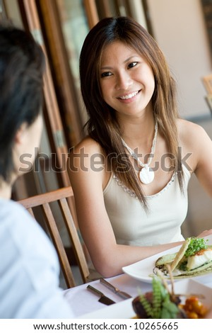 A young woman enjoying a meal at outdoor restaurant