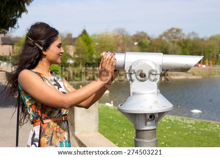 a young woman enjoying a view with a telescope - stock photo