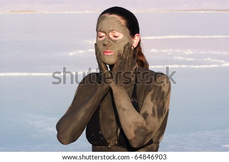 A young woman enjoying the natural mineral mud sourced from the dead sea, Israel. The Dead Sea known for its healthy minerals and as the lowest point on earth.(1,300 feet below sea level) - stock photo