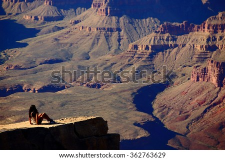 A young woman enjoys the scenic view of Grand Canyon national park, Arizona, USA - stock photo