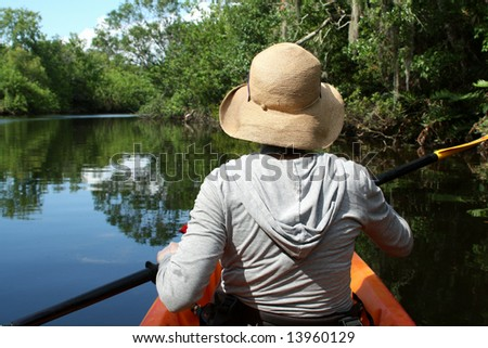 A young woman exploring a florida swamp in a kayak on a sunny day.  Melbourne, Florida. - stock photo