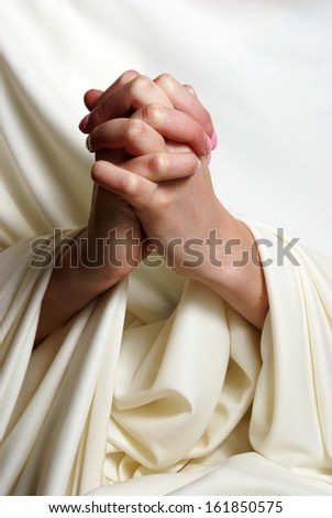 A young woman faithfully brings her hands together in essence of prayer. - stock photo