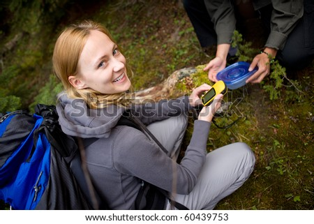A young woman finding a geocache in the forest - stock photo