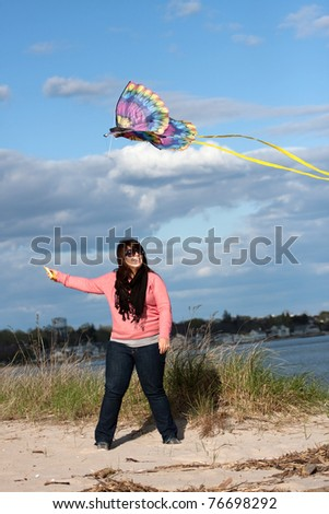 A young woman flies a kite at the beach on a nice day. - stock photo