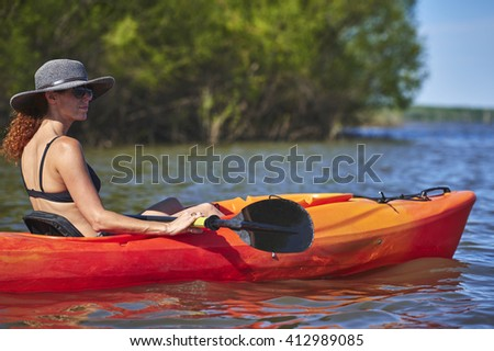 a young woman floating in a kayak - stock photo