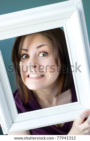 A young woman framed by a vintage white photo frame making a silly face. - stock photo