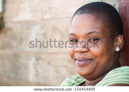 A young woman from the shacks against the wall. - stock photo