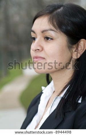 A young woman gazing off into the distance with a pensive look on her face. - stock photo