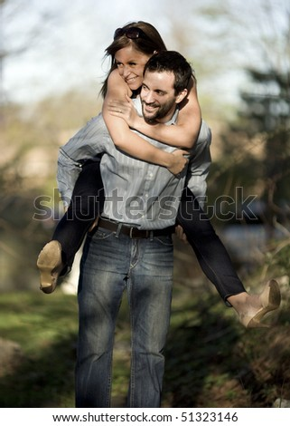 A young woman gets a piggyback ride from her male friend. - stock photo