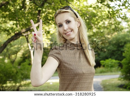 A young woman gives the peace sign.
