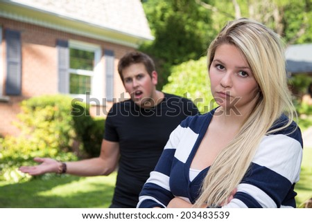 A young woman glares at the camera while her boyfriend gestures angrily in the background. - stock photo