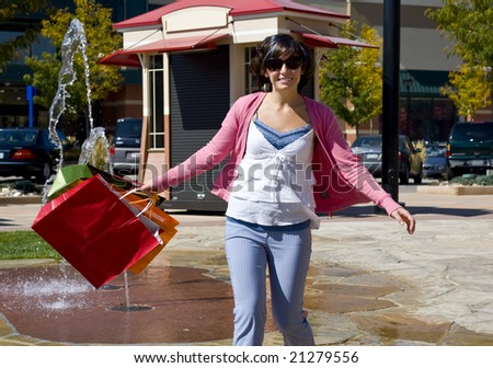 A young woman happily shopping and swinging bags by a fountain - stock photo