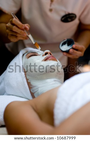 A young woman has a facial treatment at a spa