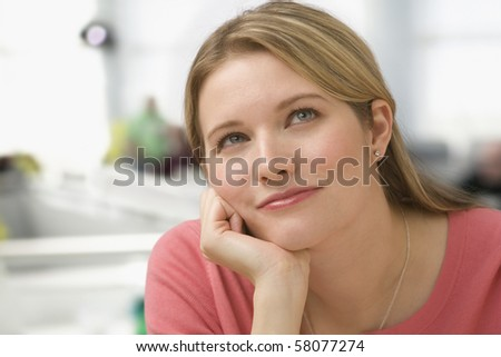 A young woman has her hand on her chin as she thinks.  She is looking away from the camera.  Horizontal shot.