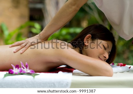 A young woman having a back massage outside in tropical setting - stock photo