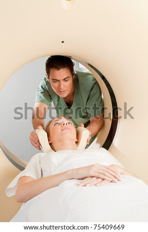 A young woman having a CT scan taken - Nurse getting things prepared - stock photo