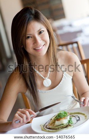 A young woman having dinner at a restaurant - stock photo