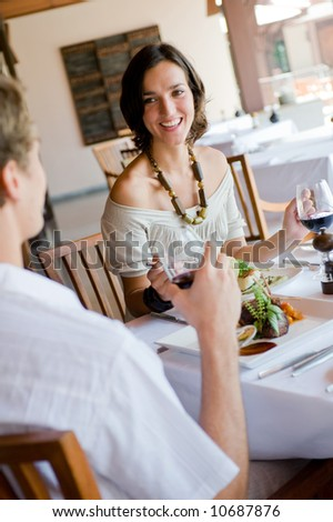 A young woman having dinner with a male partner - stock photo