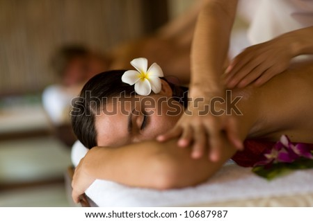 A young woman having massage in tropical spa - stock photo