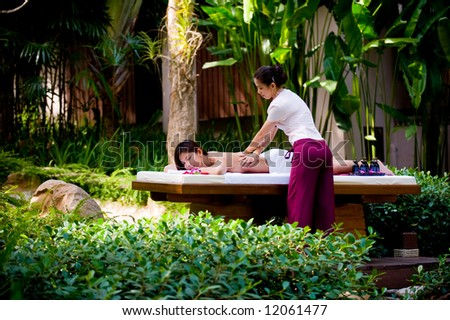 A young woman having massage outside in tropical garden