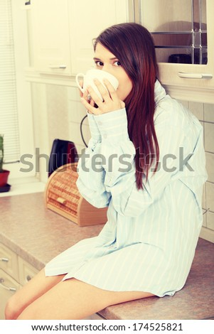 A young woman having morning coffee or tea in the kitchen