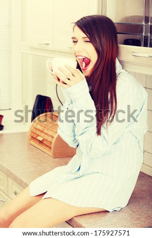 A young woman having morning coffee or tea in the kitchen  - stock photo