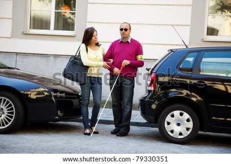 A young woman helps a man on the street - stock photo