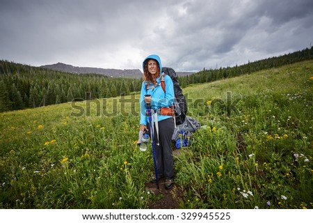 a young woman hiking in the rain - stock photo