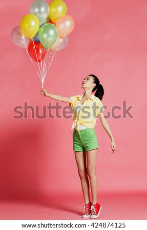 A young woman holding a balloon - stock photo