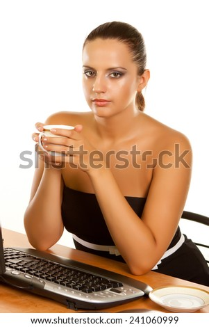 A young woman holding a cup of coffee at her workplace on a white background - stock photo