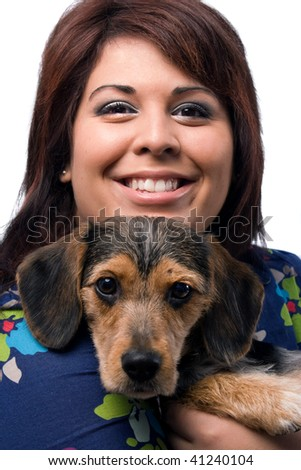 A young woman holding a cute mixed breed puppy isolated on a white background. The dog is half beagle and half yorkshire terrier.