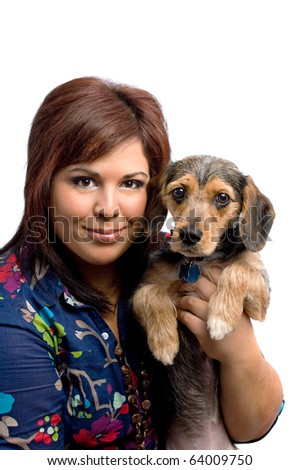 A young woman holding a cute mixed breed puppy isolated on a white background. The dog is half beagle and half yorkshire terrier. - stock photo