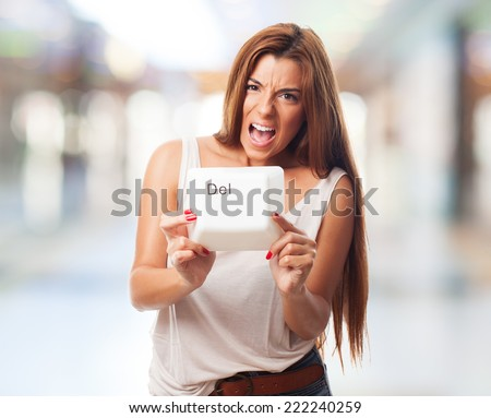 A young woman holding a delete key of a keyboard - stock photo