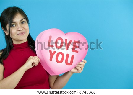 A young woman holding a large paper valentine taken on a blue background with copy space. - stock photo
