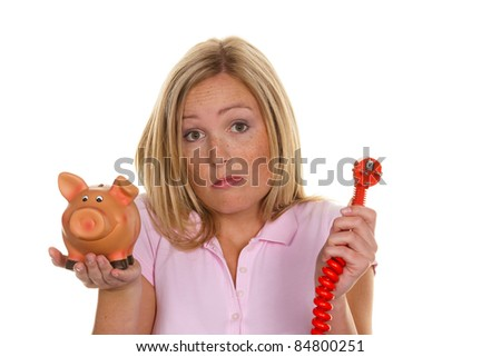 a young woman holding a piggy bank and a power plug. symbolic photo for energy cost - stock photo