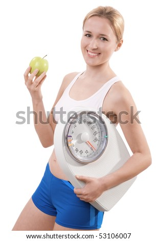 A young woman holding a weight scale and an apple