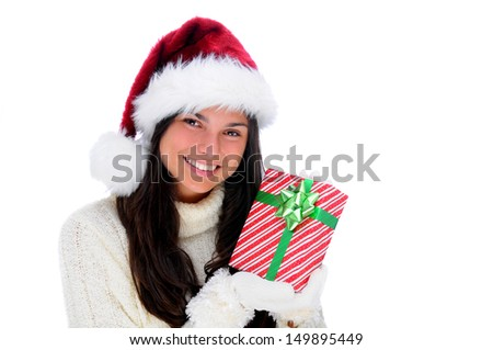 A young woman holding a wrapped Christmas present close to her face.The woman is looking towards the viewer and smiling. She is wearing a white knit sweater, Santa hat and gloves.