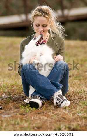a young woman holding an American Eskimo dog - stock photo