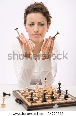 a young woman holding chess pieces - stock photo