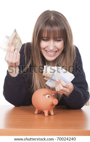 a young woman holding euro notes with a pig bank on the table - stock photo