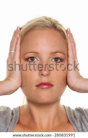 a young woman holding her ears. symbolic photo for not want to hear disputes and conflicts, as well as loud undtinnitus - stock photo