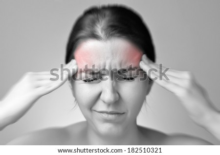 A young woman holding her painful head - stock photo