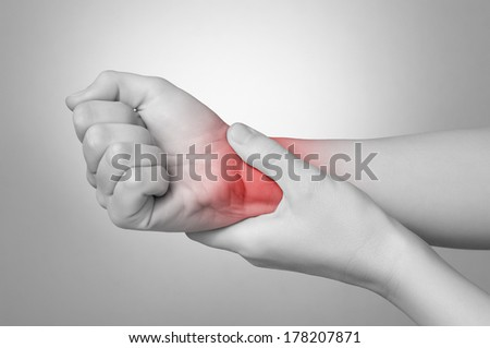 A young woman holding her painful wrist - stock photo