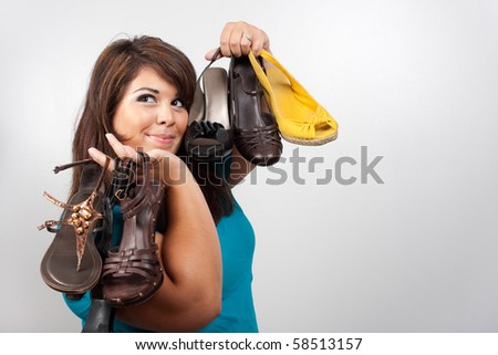A young woman holding many different shoes over a silver background.