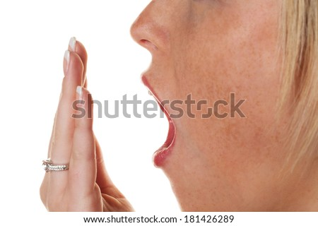 a young woman holding on while yawning hand to her mouth. fatigue and lack of sleep - stock photo