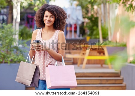 A young woman holding shopping bags and coffee outdoors - stock photo