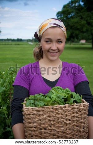 A young woman holds a basket full of fresh picked spinach greens.