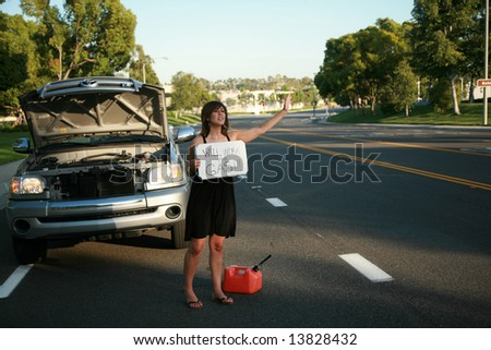 """a young woman holds a """"will work for gas"""" sign - stock photo"""