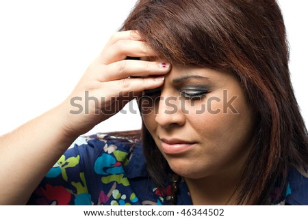A young woman holds her hand on her forehead due to a painful headache or migraine. - stock photo